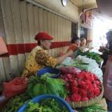Sanema, pedagang bunga di trotoar depan Pasa baru, sedang melayani pembeli (Agus Salam/Jatim TIMES)