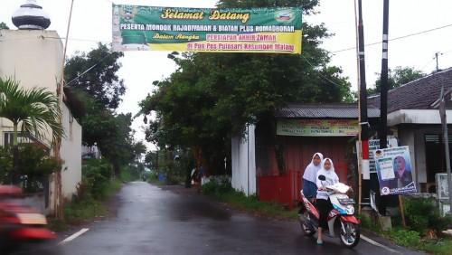 Spanduk yang dipasang di gang untuk menyambut jemaah dari PP Miftahu Falahi Mubtadi'ien dusun Sukosari, Desa Purwosari, Kecamatan Kasembon, Kabupaten Malang
