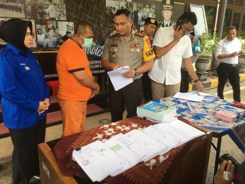 Kepala Desa Balearjo Riduan, tersangka kasus tindak pidana korupsi saat sesi rilis di halaman Polres Malang, Kabupaten Malang (Foto : Ashaq Lupito / MalangTIMES)