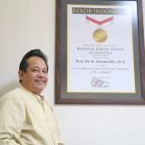 Prof. Dr. Ishomuddin, M.Si. tengah menunjukan piagam MURI yang diterimanya baru-baru ini. (Foto: Mirza/ Humas UMM)