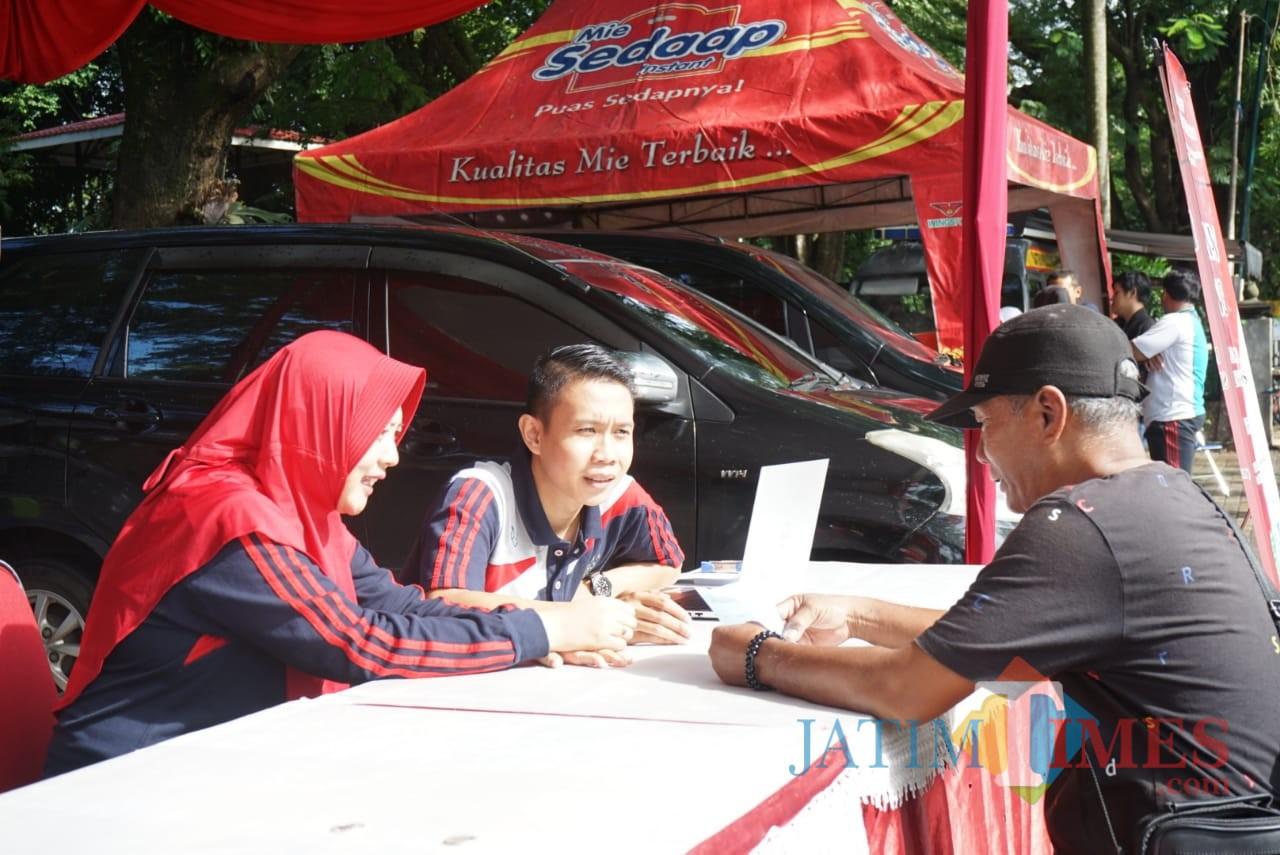 Salah satu warga saat membayar denda tilang di acara CFD. (foto: Joko Pramono/Jatim times)