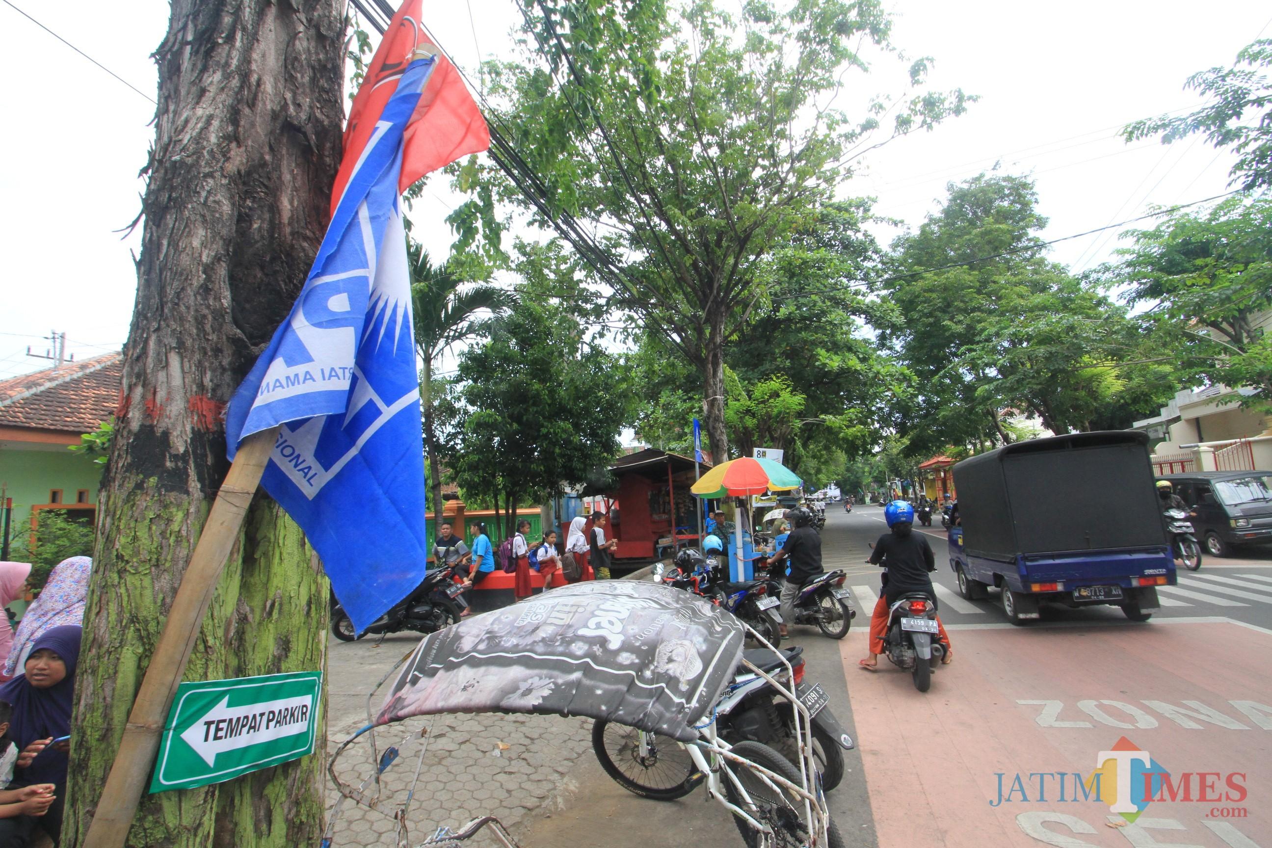 Bendera Parpol terpampang di depan SDN Kebonsari Kulon 1 (Agus Salam/Jatim TIMES)