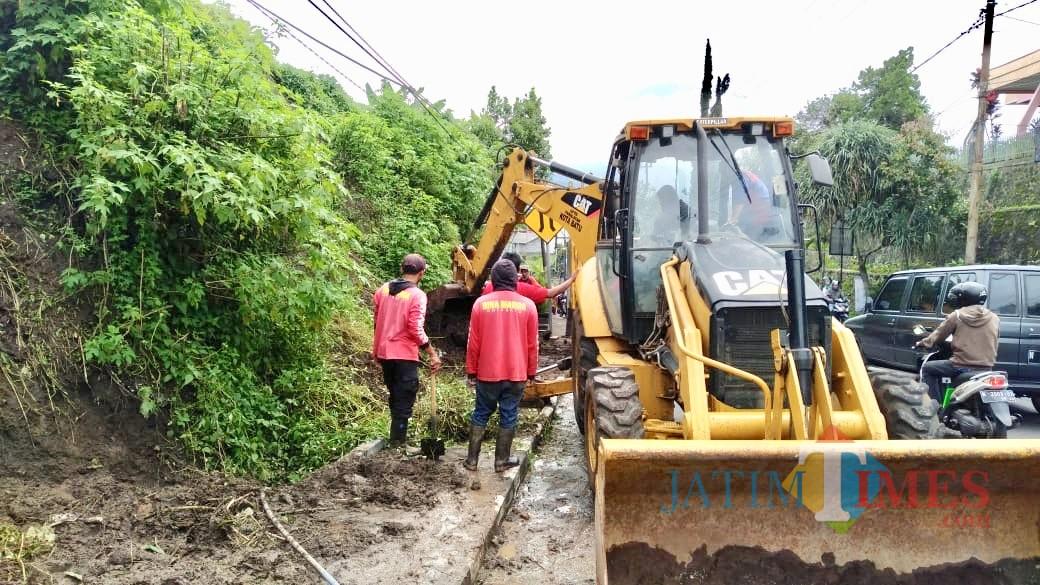 Alat berat didatangkan untuk mengatasi tanah longsor yang menutup drainase di Jalan Brantas, Kelurahan Sisir, Kecamatan Batu,Selasa (19/3/2019). (Foto: Ist)