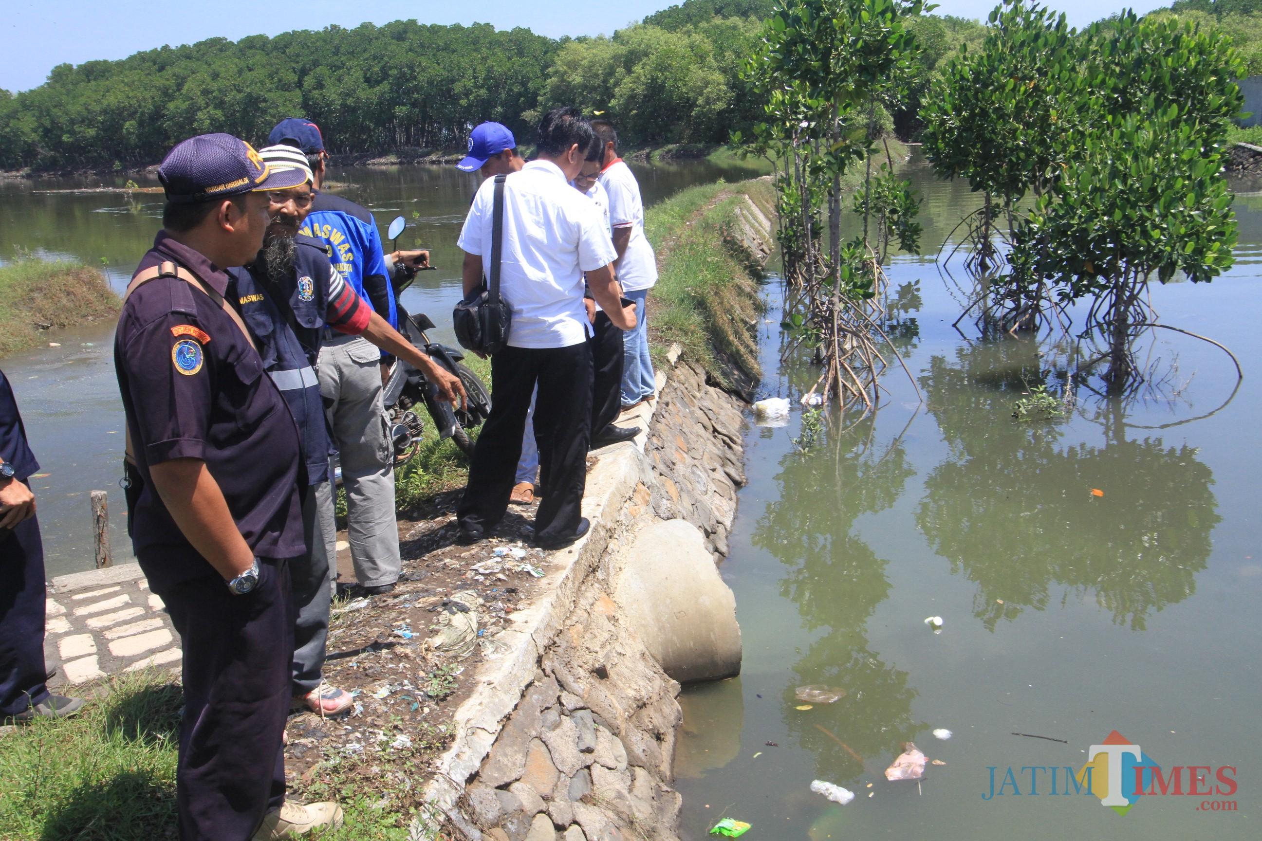 Petugas dari DKP dan DLH Jatim Melihat pembuangan limbah PT AFU  (Agus Salam/Jatim TIMES)
