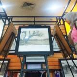 Salah satu pengunjung melihat foto tentang sejarah jembatan lama. (Eko Arif S /JatimTIMES)