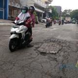 Kondisi jalan berlubang di Kota Malang yang secara swadaya ditambal menggunakan batako oleh warga. (Foto: Nurlayla Ratri/MalangTIMES)