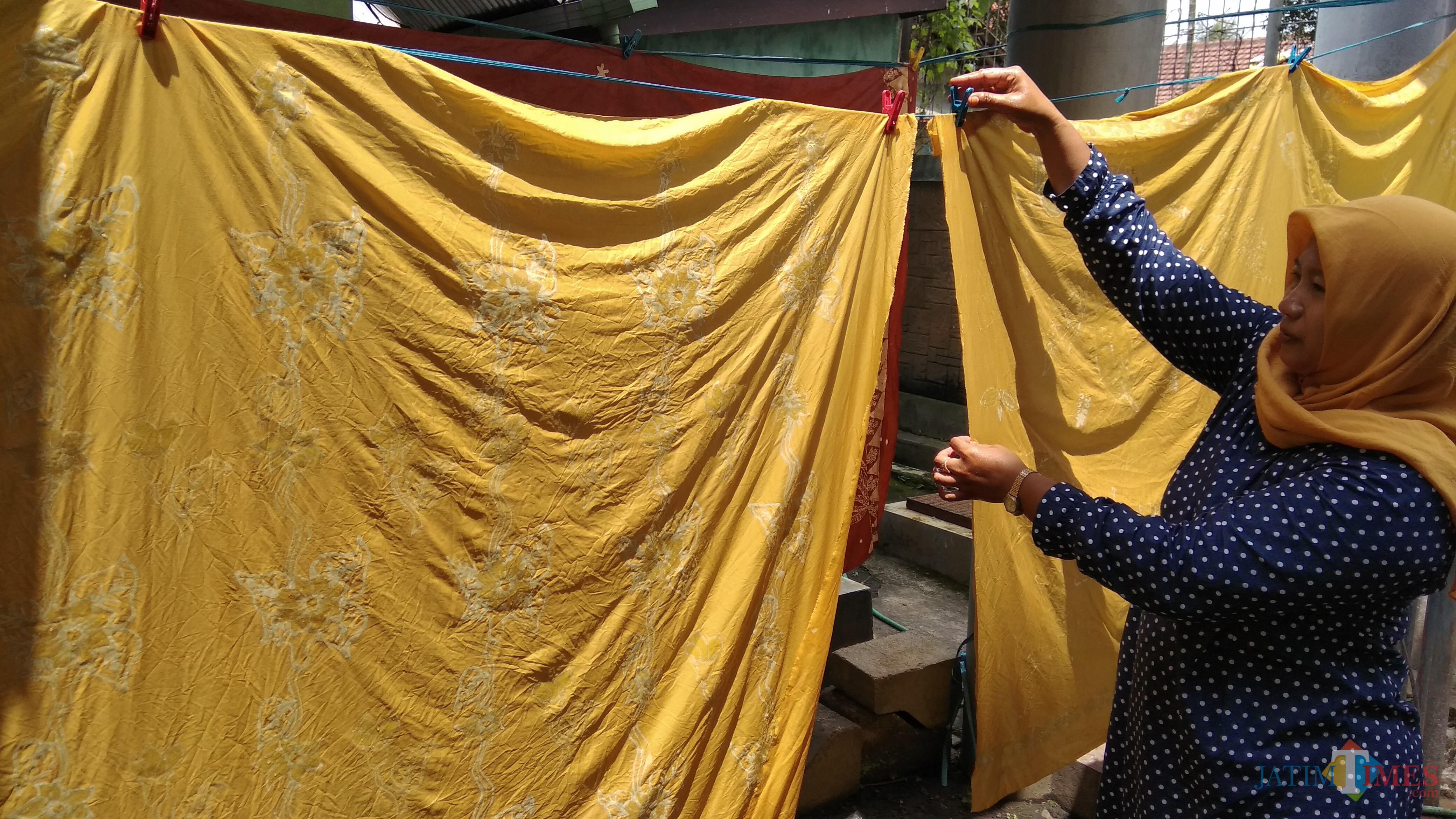 Peserta pelatihan tengah menjemur kain batik tulis yang menggunakan pewarna alami. (Foto: Nurlayla Ratri/MalangTIMES)