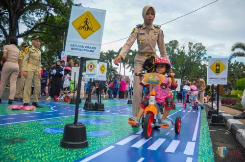 Seorang anak yang ikut serta belajar berlalu lintas yang baik di taman lalu lintas yang disediakan Kemenhub RI di Jalan Ijen Kota Malang. (Luqmanul Hakim/Malang Times)
