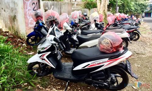 Helm yang terdapat di atas sepeda motor tertutup kantong plastik merah yang terparkir di area SMAN 1 Batu. (Foto: Irsya Richa/MalangTIMES)