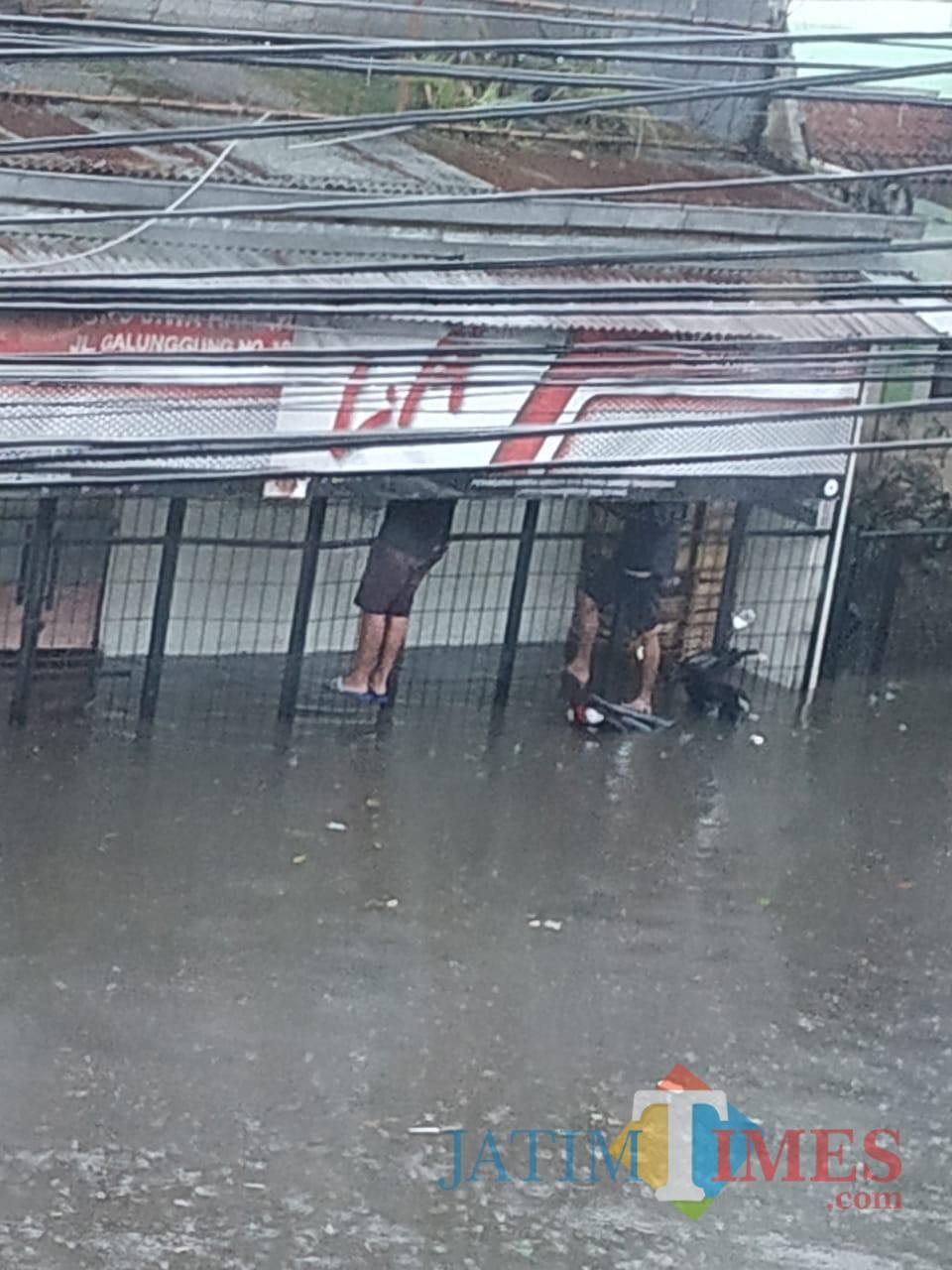 Warga memilih memanjat pagar untuk menghindari banjir yang terjadi di Kota Malang. (Foto: Dokumen MalangTIMES)
