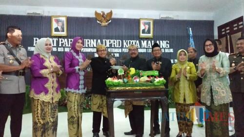 Ketua DPRD Kota Malang, Bambang Heri Susanto (kanan) menyerahkan potongan tumpeng pertama kepada Wali Kota Malang dalam perayaan HUT ke 105 Kota Malang (Pipit Anggraeni/MalangTIMES)