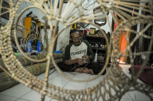 Samsul Subakri atau Mbah Kardjo saat membuat Wayang Suket di kediamannya yang terletak di Jl bantaran sungai Brantas dibawah jembatan Soekarno Hatta Kota Malang