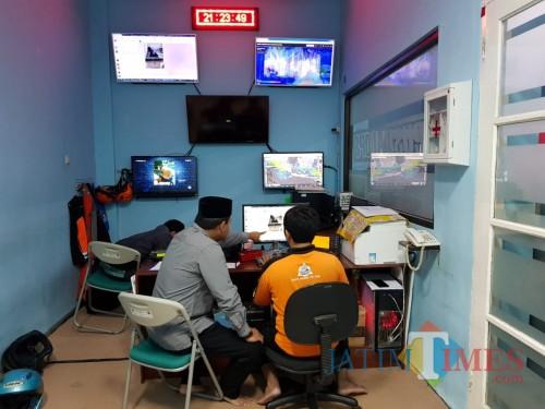 Plt Kepala BPBD Kota Malang Handi Priyanto (kiri) melakukan monitoring potensi bencana di kantor Pusdalops PB Kota Malang. (Foto: Dokumen MalangTIMES)