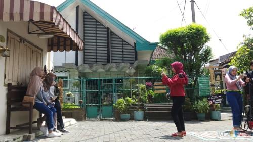 Wisatawan yang tengah berfoto dengan background rumah lawas dan rumah jengki di Kampung Heritage Kayutangan (foto: Pipit Anggraeni/MalangTIMES).