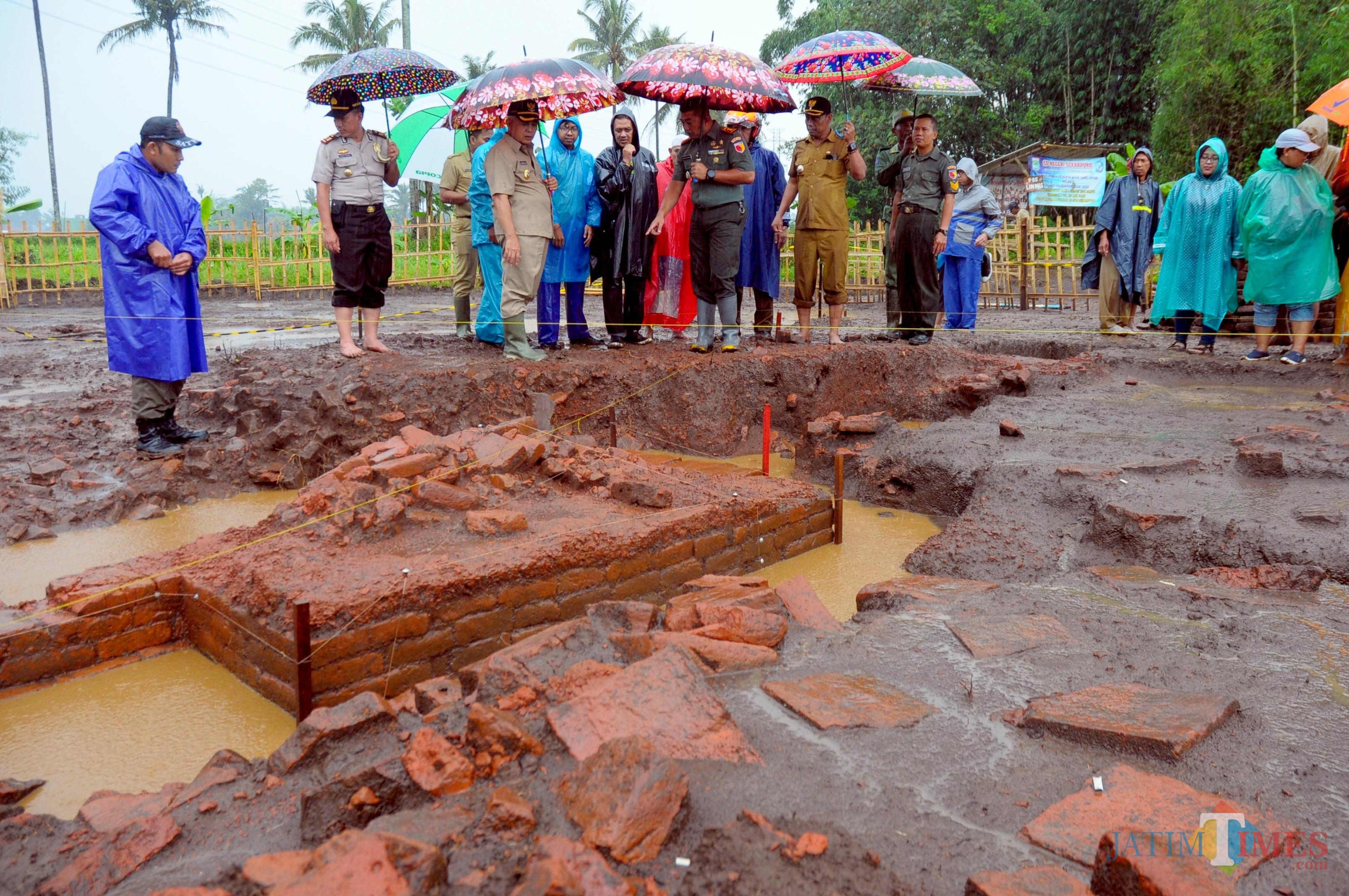 Plt Bupati Malang didampingi oleh Muspika saat meninjau situs Sekaran ditengah hujan (Luqmanul Hakim/Malang Times)