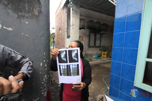 Yuli Era menunjukkan foto jalan kecil yang ditutup dengan sesek bambu di jalan oleh keluarga Sanali  (Agus Salam/JatimTIMES)