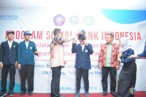 Penyematan topi oleh Deputi Kepala Perwakilan Tim Ekonomi Bank Indonesia KPW Malang Jaka Setyawan sebagai simbolis terhadap mahasiswa yang akan tergabung dalam program GenBI. (Luqmanul hakim/Malang Times)
