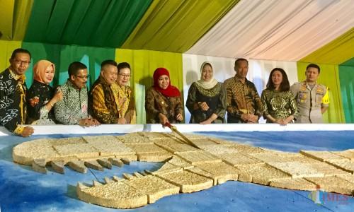 Gubernur Jatim Khofifah Indar Parawangsa memotong tempe, Sabtu (6/4/2019). (Foto: Irsya Richa/MalangTIMES)