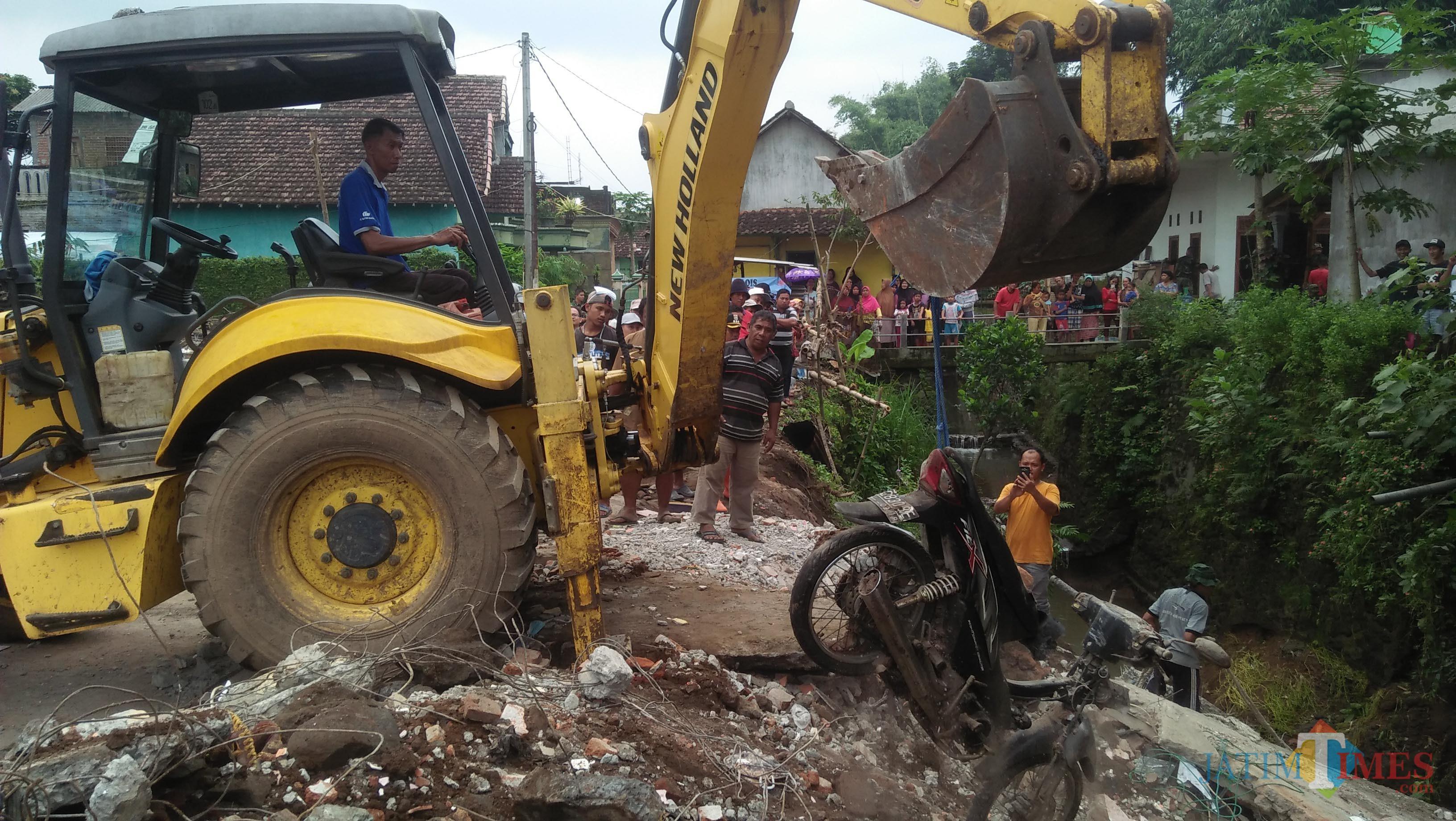 Pengangkatan motor terakhir penghuni rumah kos yang ambruk di Desa Losari Kecamatan Singosari dengan menggunakan alat berat milik TPU. (Luqmanul Hakim/Malang Times)
