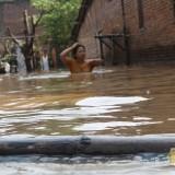 Salah seorang warga Dusun Kebondalem, Desa Kademangan terlihat berjalan di tengah-tengah banjir setinggi satu mater. (Foto: Adi Rosul / JombangTIMES)
