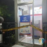 Polisi memasang police line di ATM yang bermasalah.