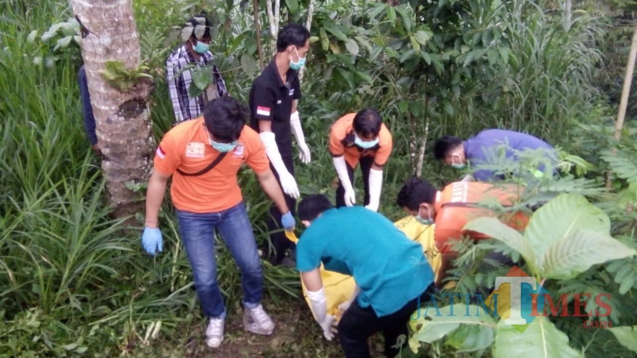 Petugas mengevakuasi jasad jamal setelah ditemukan di pekarangan rumah / Foto : Dokpol / Tulungagung TIMES