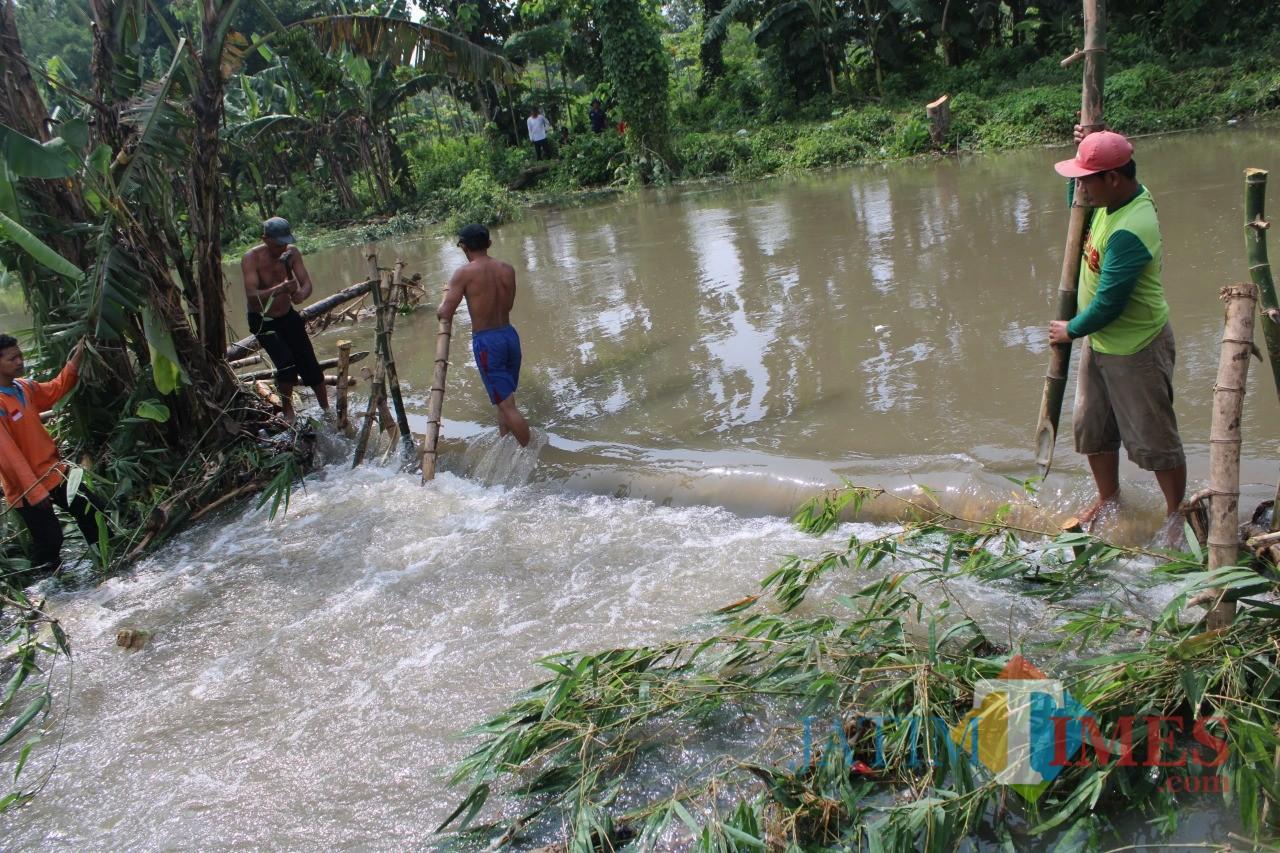 Sejumlah warga Desa Kedunglosari tampak bergotong-royong membendung tanggul yang jebol. (Foto : Adi Rosul / JombangTIMES)