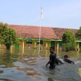 Kondisi SDN 2 Perak terendam banjir, sejumlah siswa terlihat bermain air di halaman sekolah. (Foto : Adi Rosul / JombangTIMES)