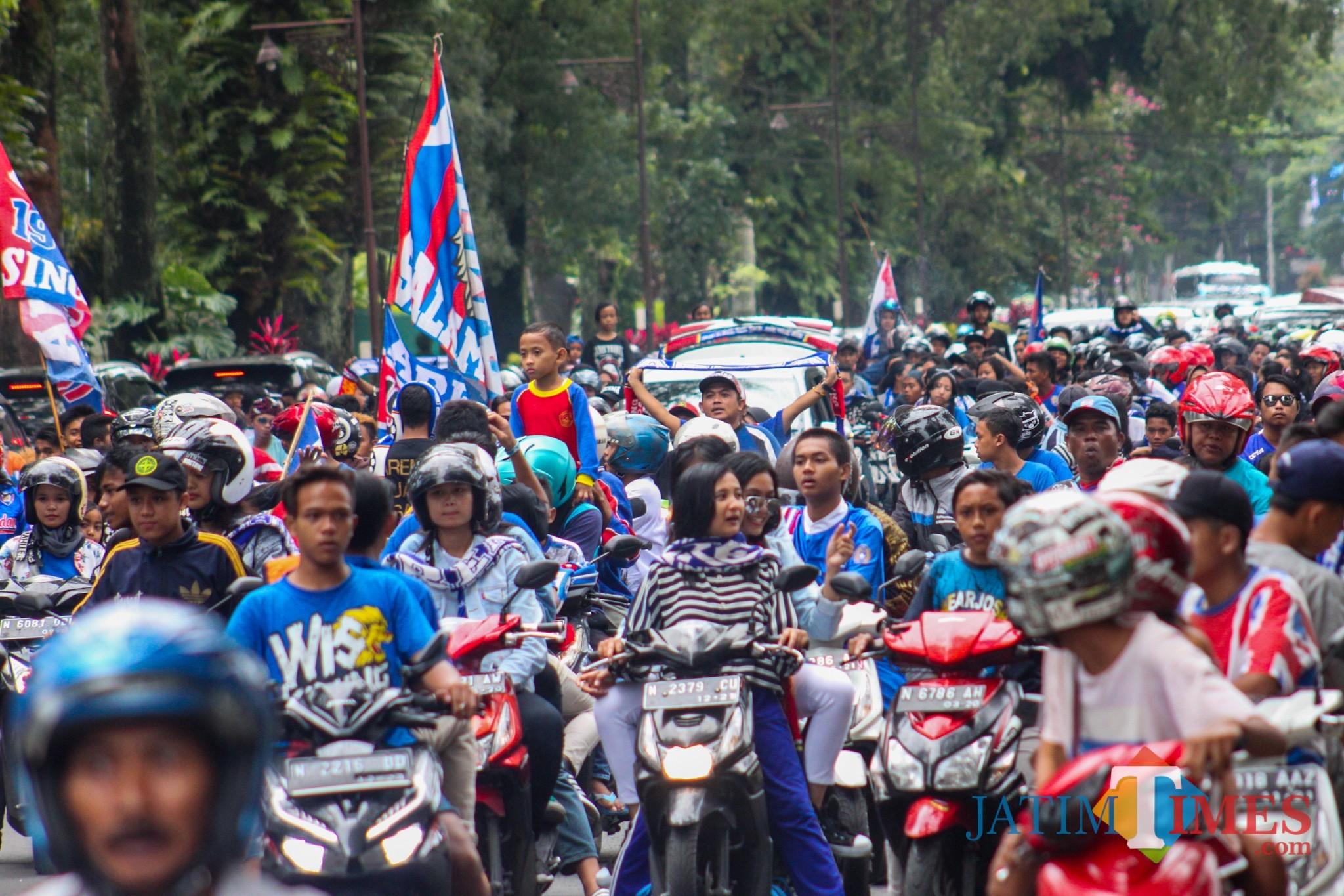 Supporter Arema pada saat berkonvoi di jalanan Kota Malang (Luqmanul Hakim/Malang Times)