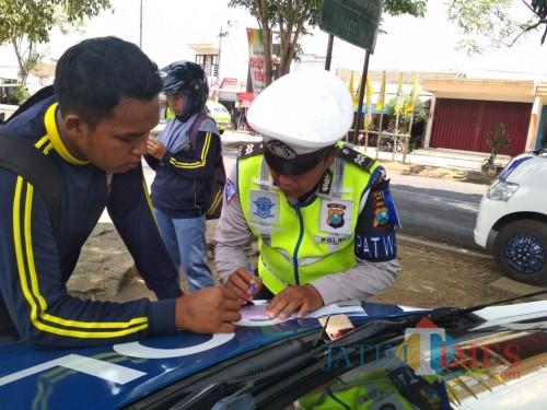 Ilustrasi petugas kepolisian saat memberikan surat tilang kepada pelajar yang tidak memiliki SIM, Kabupaten Malang (Foto : Dokumen MalangTIMES)