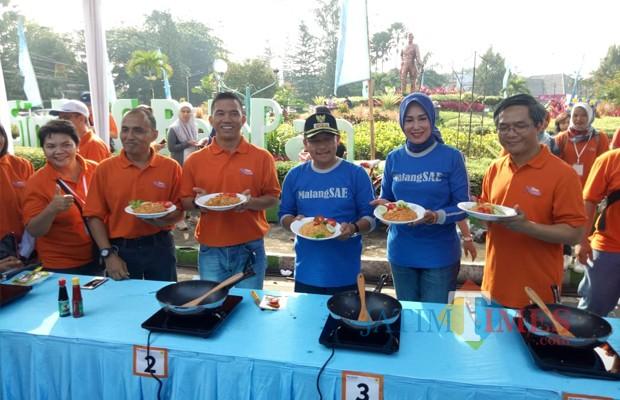 Wali Kota Malang Sutiaji beserta istri, Widayati Sutiaji (tengah kenalan baju warna biru) saat melakukan demo masak nasi goreng untuk mengkampanyekan hemat energi menggunakan kompor induksi (Humas Pemkot Malang for MalangTIMES).