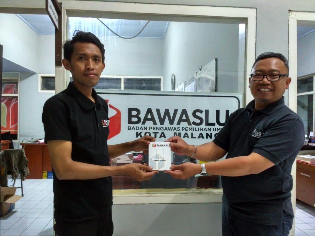 Muhammad Faris Abdul Aziz dari Bawaslu Jatim menyerahkan Kartu Identitas Pemantau kepada Felik Sad Windu selaku koordinator pemantau dari Ma Chung. (Foto: Humas)