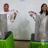 Wali Kota Batu Dewanti Rumpoko (kiri) bersama putrinya Ganis Rumpoko (kanan) menunjukkan surat suara seusai melakukan pencoblosan (Luqmanul Hakim/Malang Times)