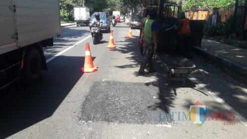 Jalan berlubang yang banyak memakan korban di Jalan Soekarno-Hatta akhirnya diperbaiki  (Agus Salam/Jatim TIMES)