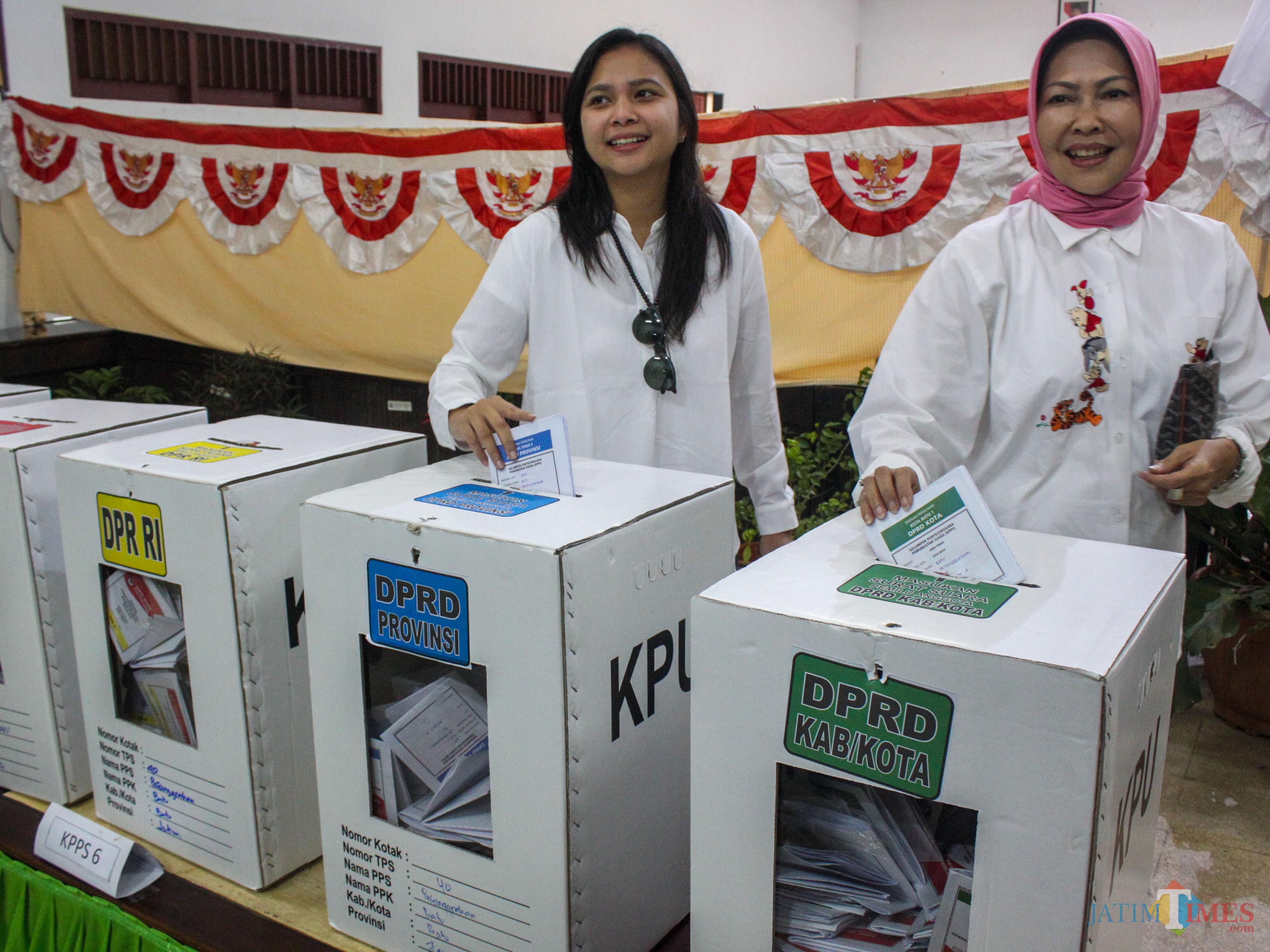 Ganis Rumpoko (kiri) dan Wali Kota Batu Dewanti Rumpoko (kanan) memasukkan surat suara di TPS di Kota Batu (Luqmanul Hakim/Malang Times)