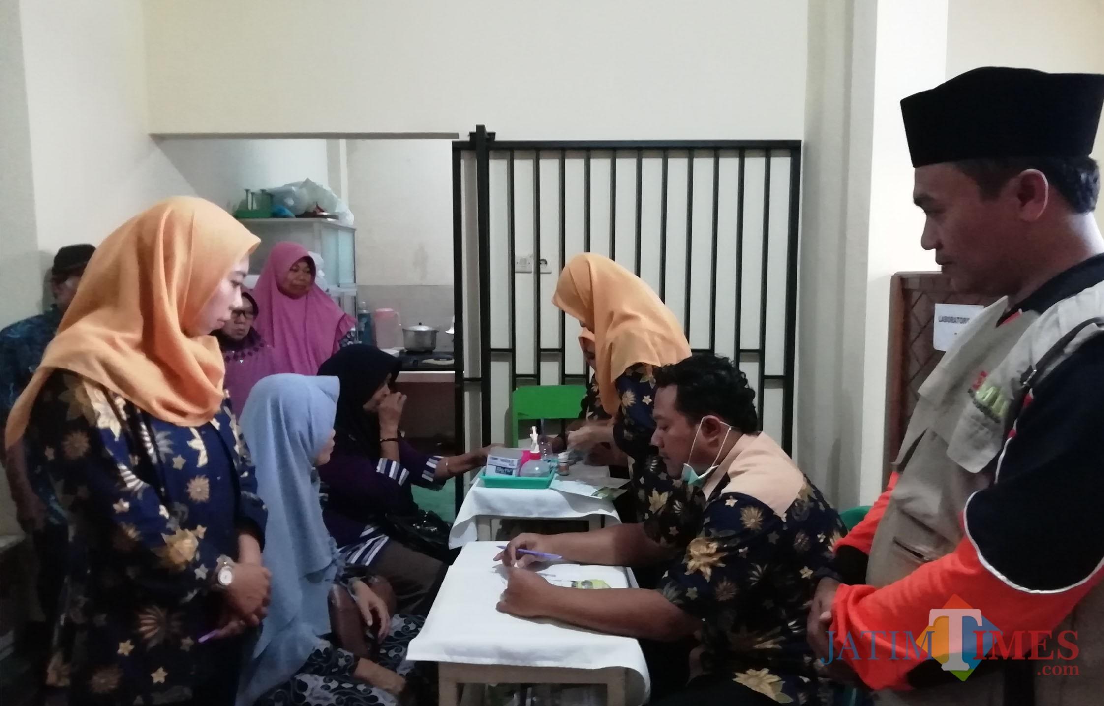 Kiri : Ernis Widyalistanti Ketua Panitia Pengobatan Gratis bersama Ruwiyanto (kanan) dari BMH saat melihat warga cek kesehatan gratis (Nana)
