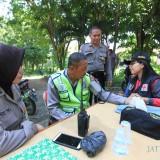 Salah satu anggota yang menjaga rekapitulasi suara di Kecamatan Kedopok tengah diperiksa kesehatannya oleh dokpol. (Agus Salam/Jatim TIMES)