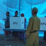 Pemilih didampingi saat di bilik suara.
