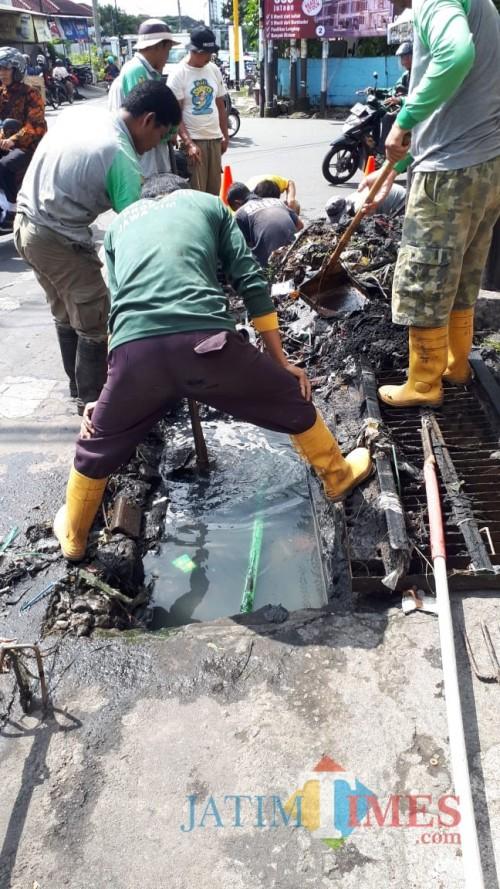 Suasana Satgas DPUPR saat membersihkan saluran yang tertimbun sampah (Hendra Saputra/ MalangTIMES)