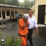 Ali Muchtar (baju oranye), tersangka kasus kekerasan dan persetubuhan terhadap anak tirinya, saat digelandang ke ruang penyidikan UPPA Polres Malang. (Foto : Ashaq Lupito / MalangTIMES)