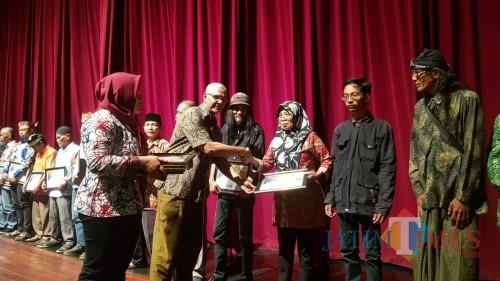 Seniman tradisi asal Malang, Sumanah saat menerima piagam penghargaan dari Sekda Pemprov Jatim Heru Tjahjono. (Foto: Dokumen MalangTIMES)