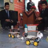 Dua orang santri Ponpes INSAT Muhammadiyah Banyuwangi sedang mengoperasikan robot buatan mereka