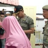 Petugas saat memeriksa identitas pengunjung hotel. (foto : Joko Pramono/Jatim Times)