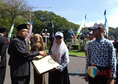 Pemenang Lomba website Journalist Camp menerima hadiah dari Mendikbud yang diserahkan oleh Ketua DPRD Kota Malang, Bambang Heri Susanto (foto: Pipit Anggraeni/MalangTIMES).