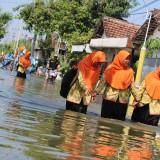 Sejumlah siswa SMPN 2 Ploso terlihat sedang berjalan di tengah-tengah banjir yang melanda desa Jatigedong, Kecamatan Ploso (Foto: Adi Rosul / JombangTIMES)
