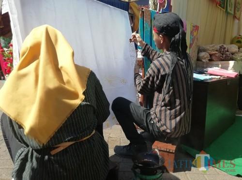 Dua pelajar kelas 9 SMP Islam Kalipare saat mempraktekkan membatik di depan standnya (Nana)