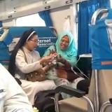 Seorang suster membagikan makanan ringan kepada seornag wanita muslim di atas kereta. (Foto: video @rfxzpt)