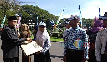 Nadya Salsabila Azzahra, perwakilan SMPN 20 Kota Malang, saat menerima hadiah laptop dari mendikbud dalam lomba website Journalist Camp 2019 pada Hardiknas Kota Malang beberapa hari lalu di Balai Kota Malang. (Pipit Anggraeni/MalangTIMES)