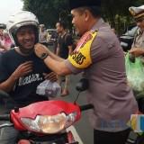 Kapolres Banyuwangi AKBP Taufik HZ memasangkan tali pengaman helm pengendara motor disela pembagian takjil gratis