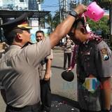 Kapolres AKBP Tofik Sukendar mengguyur air kembang pada Kompol Ki Ide Bagus Tri dalam Sertijab (foto : Anang Basso / TulungagungTIMES)